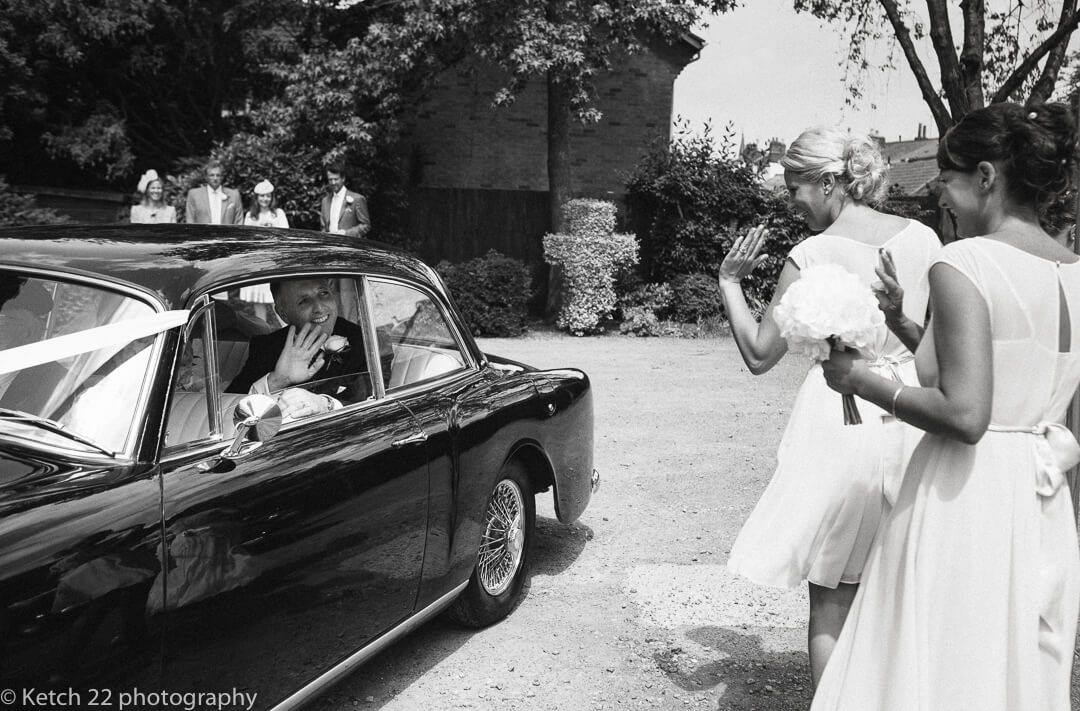 Groom waving goodbye from black wedding car