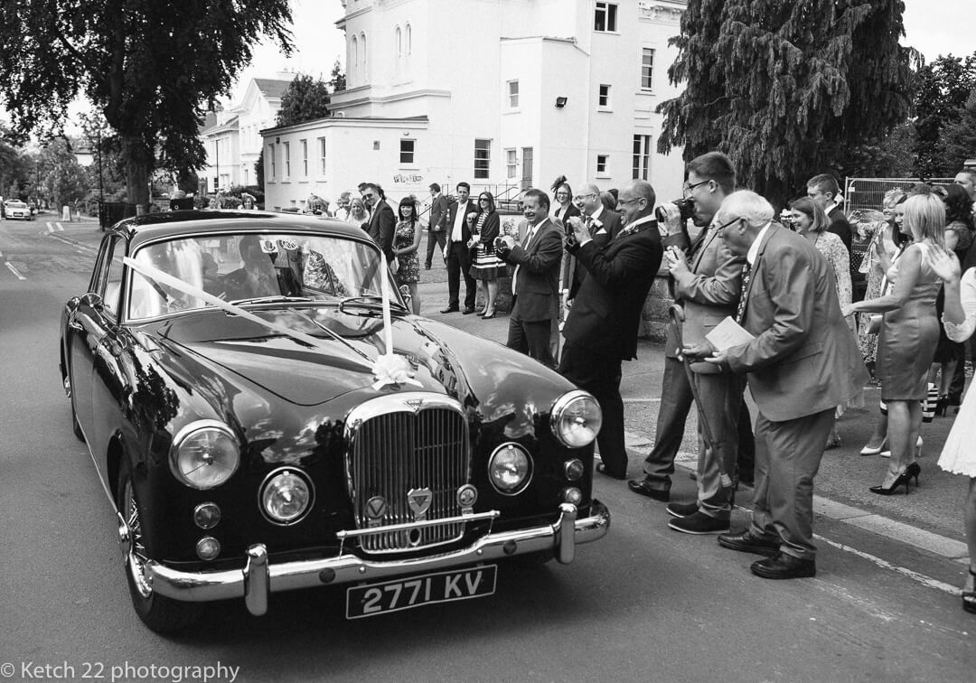 Wedding guests cheering as classic black car leaves for wedding venue