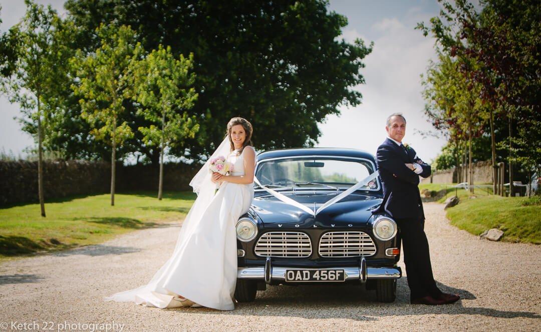 Bride and groom leaning on black vintage wedding car