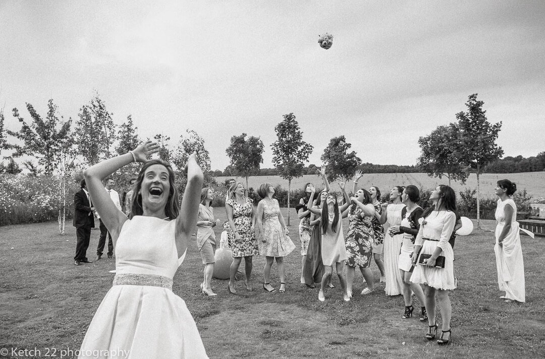 Bride throws bouquet of flowers while wedding guests try to catch it