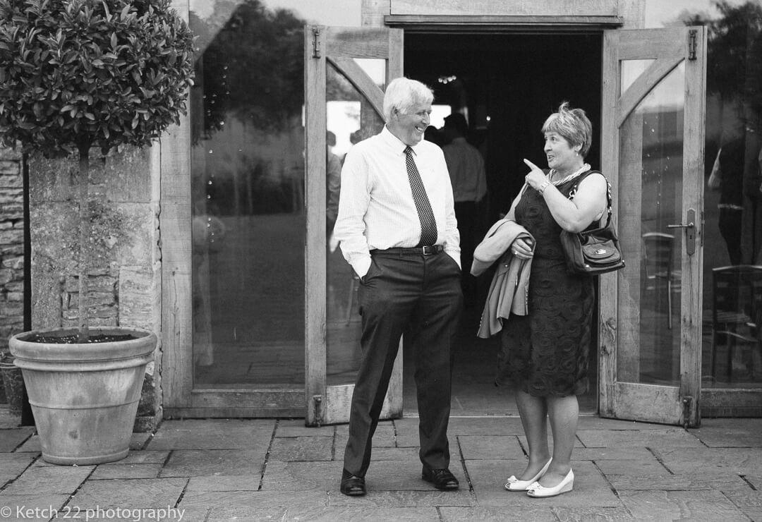 Wedding guests chat outside wedding barn
