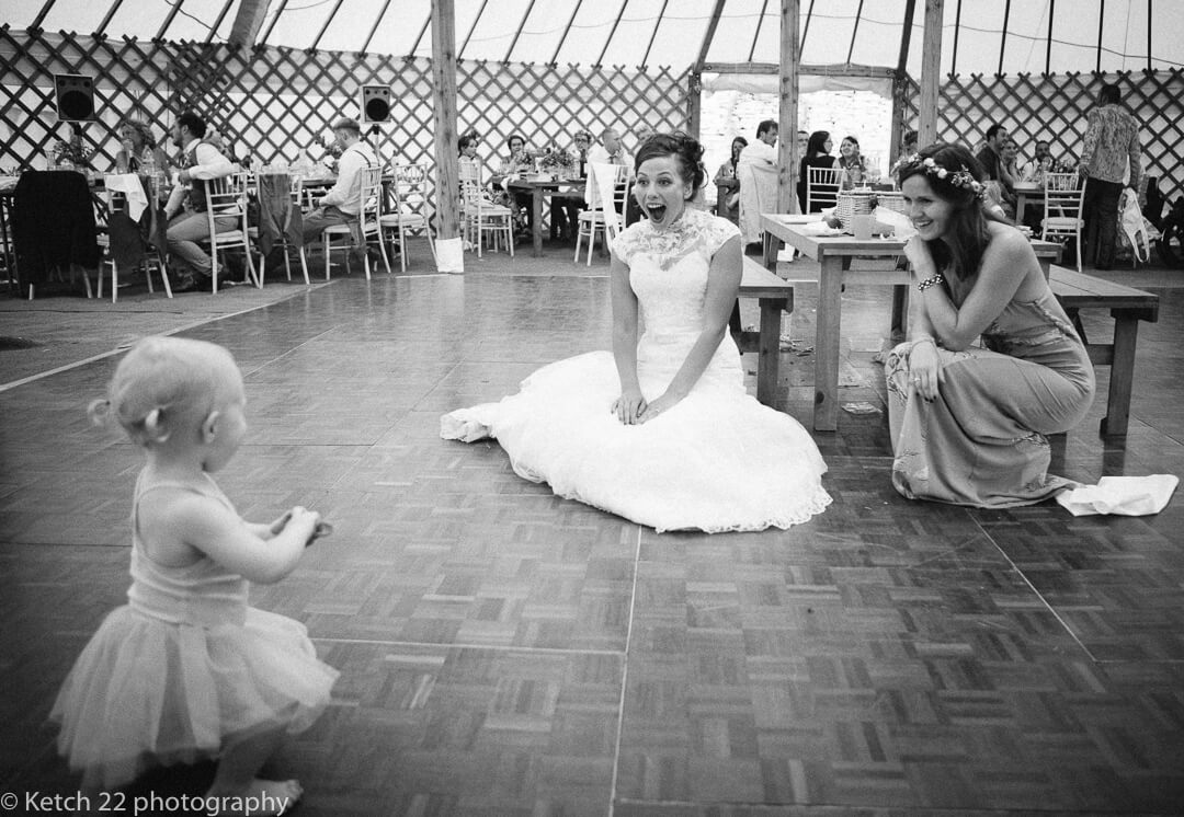 Bride playing with baby at wedding