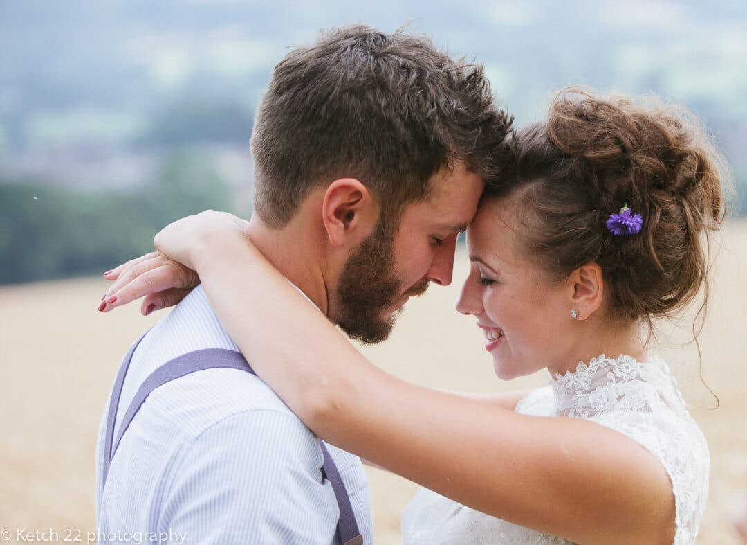 Bride and groom hugging at rural wedding