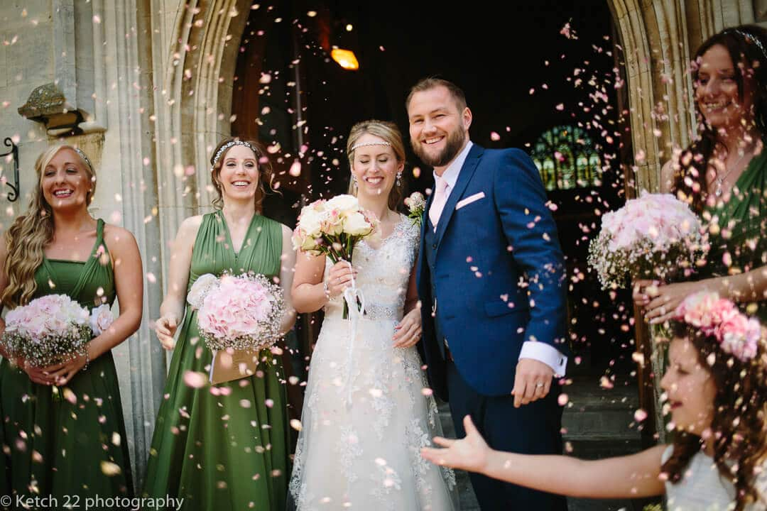 Bride and groom get showered in confetti outside church door
