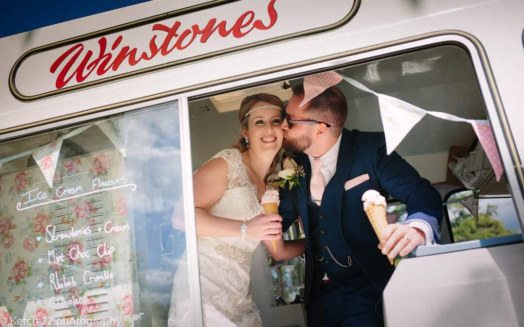 Bride and groom kissing and eating Winstones ice cream in Gloucestershire