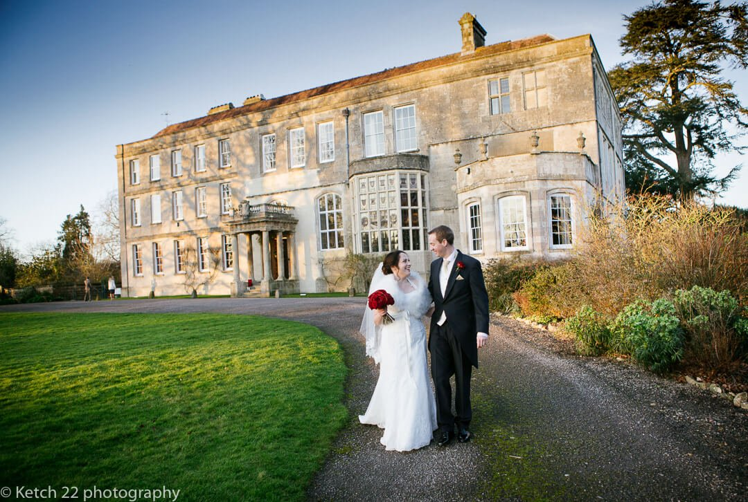 Bride and groom walking on path in front of Elmore Court wedding venue