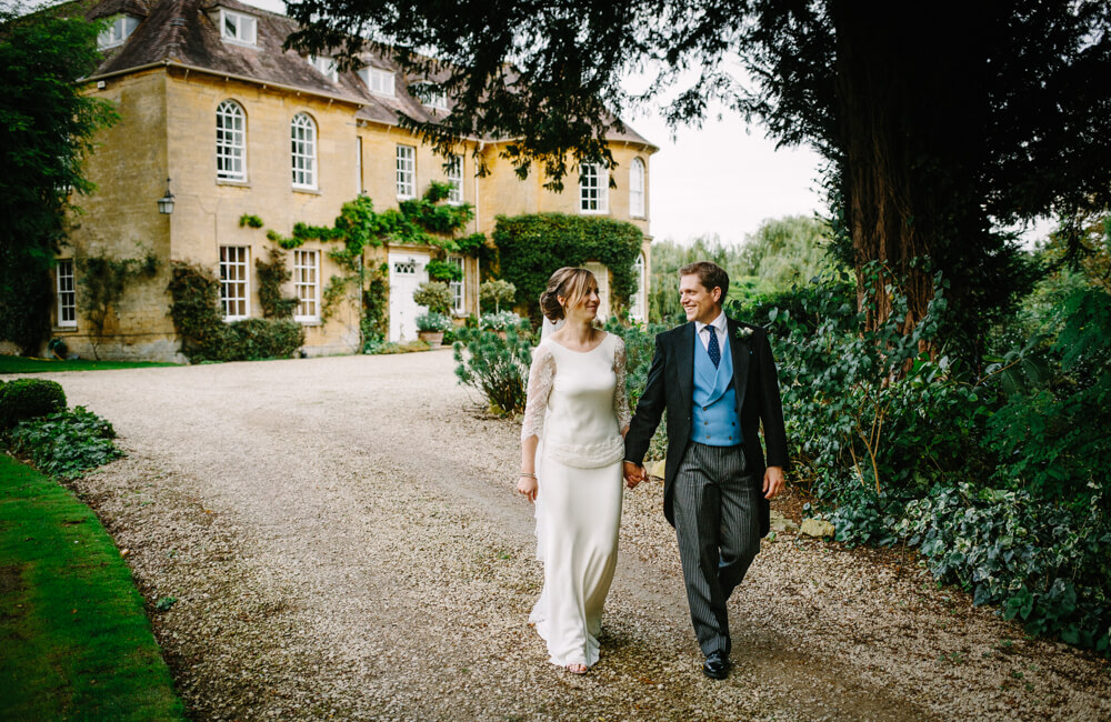 Bride and groom walking in front of Upper Court wedding venue Gloucestershire