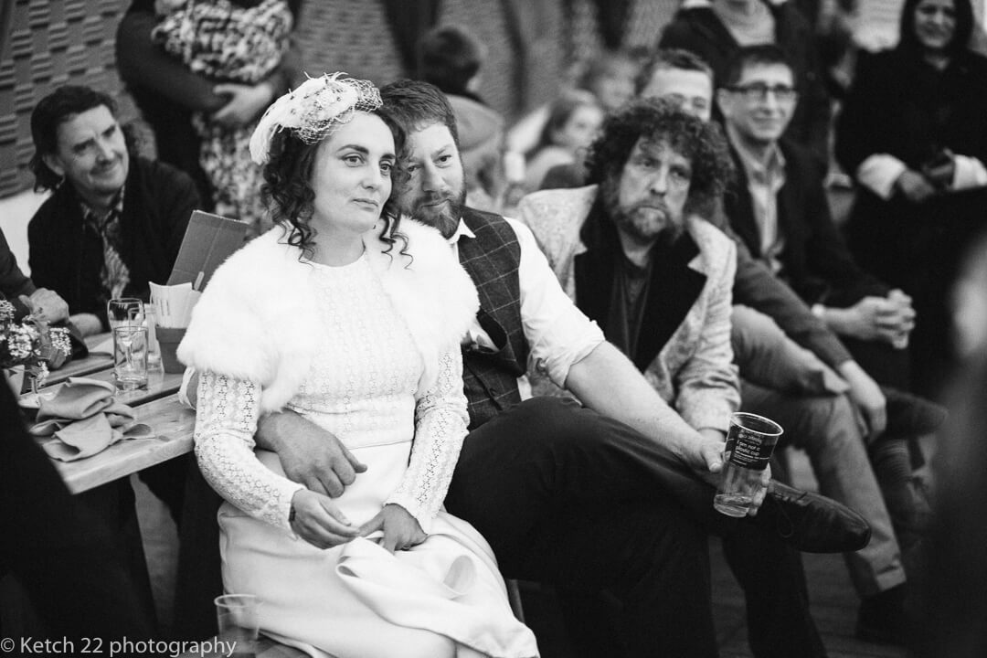 Bride and groom watching wedding speeches in marquee