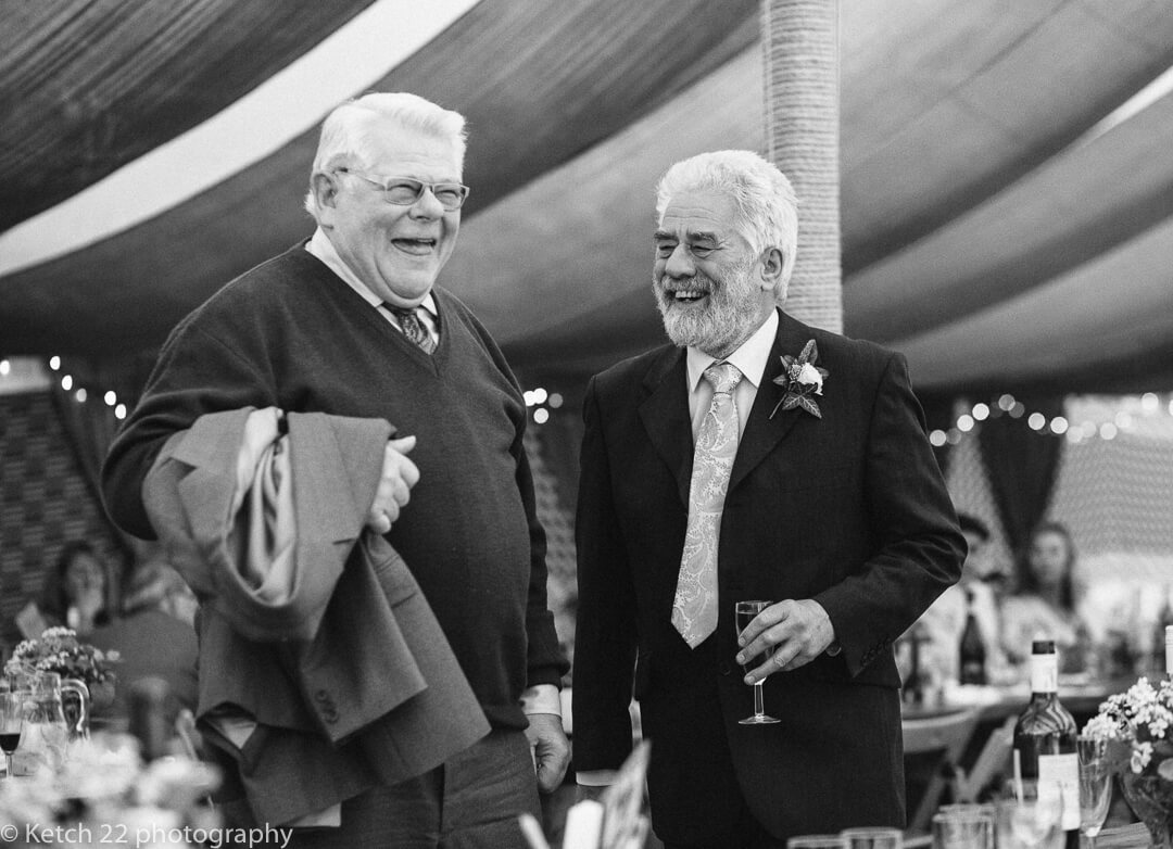 Old men chatting and laughing at wedding