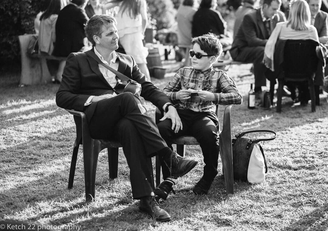 Father and sun relaxing at outdoors vintage wedding