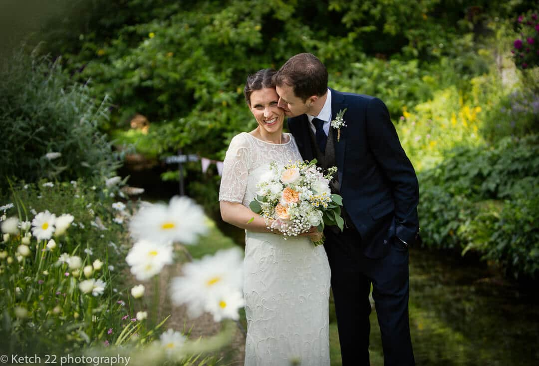 Groom kissing bride with flowers in the garden at The Swan at Bibury wedding