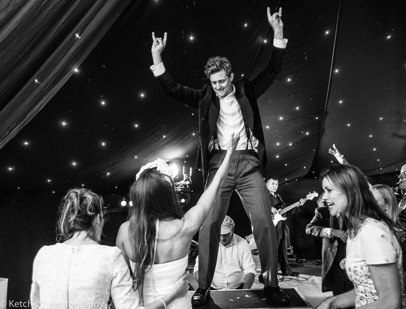 Groom dancing on piano at wedding reception in Dorset