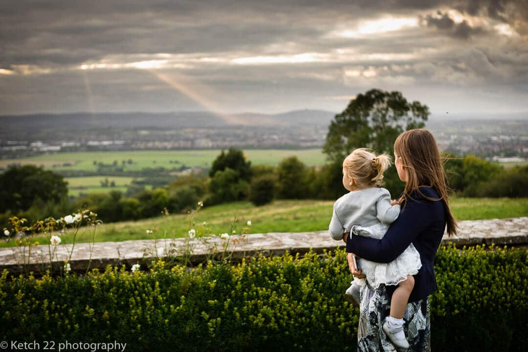 Little girl and big sister overlooking countryside at Gloucestershire wedding