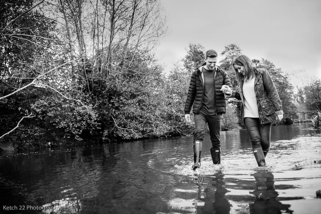 Engaged couple walking in river in Herefordshire