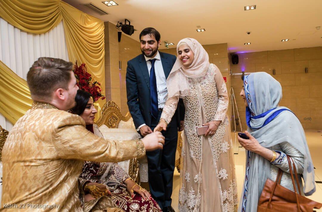 Wedding guests greeting bride and groom at muslim wedding