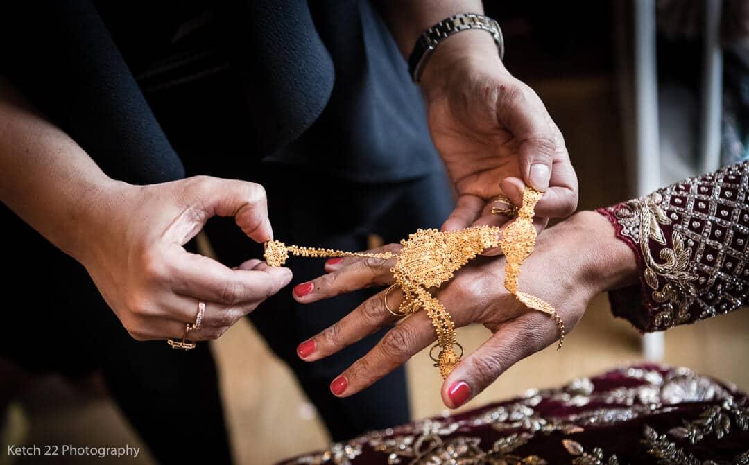 Muslim bride having jewellery put on during wedding preparations