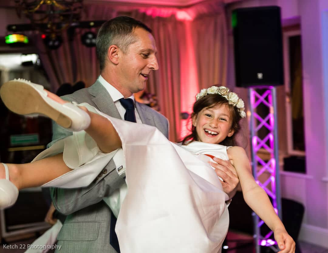 Flower girl with her father laughing at wedding reception