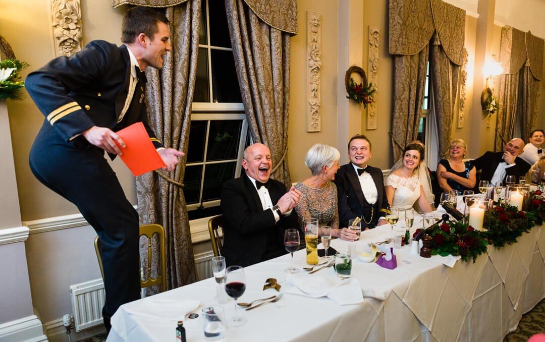 Best man standing on chair whilst making wedding speech
