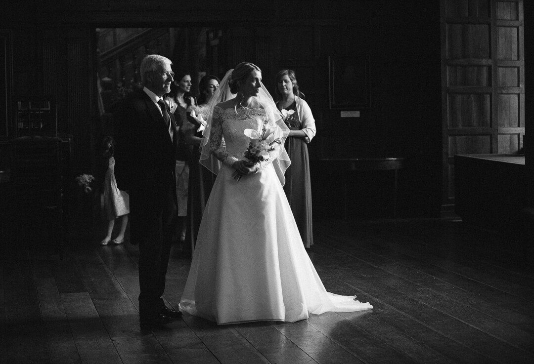 Moody black and white photo of bride waiting just before wedding ceremony