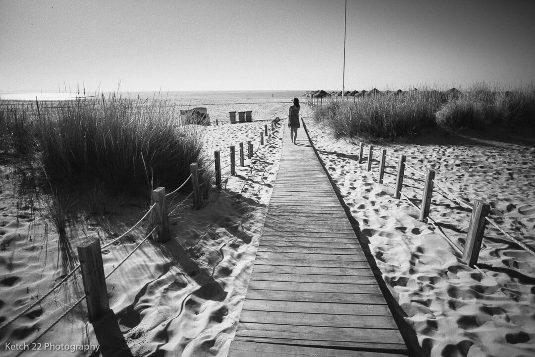 Lady on beach on wooden path