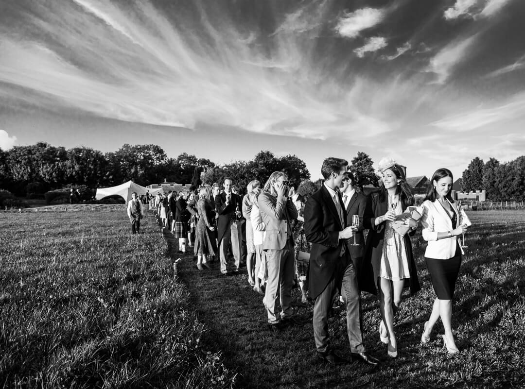 Wedding guests waiting to get into marquee at summer wedding