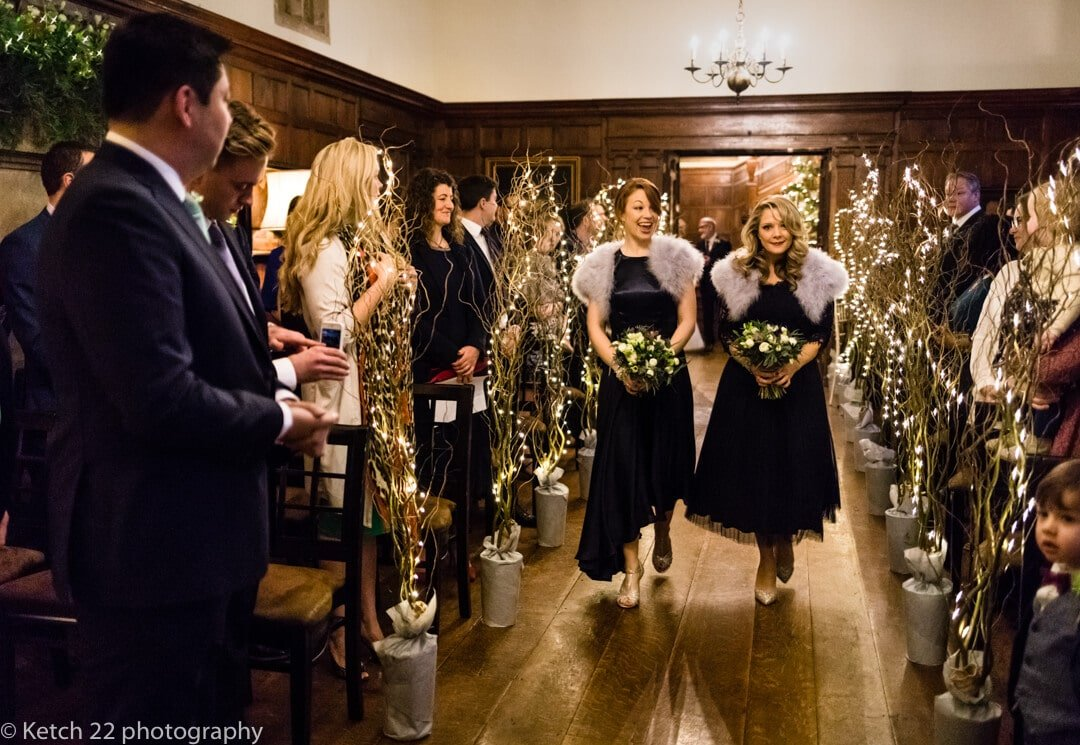 Bridesmaids walking down the aisle at winter wedding