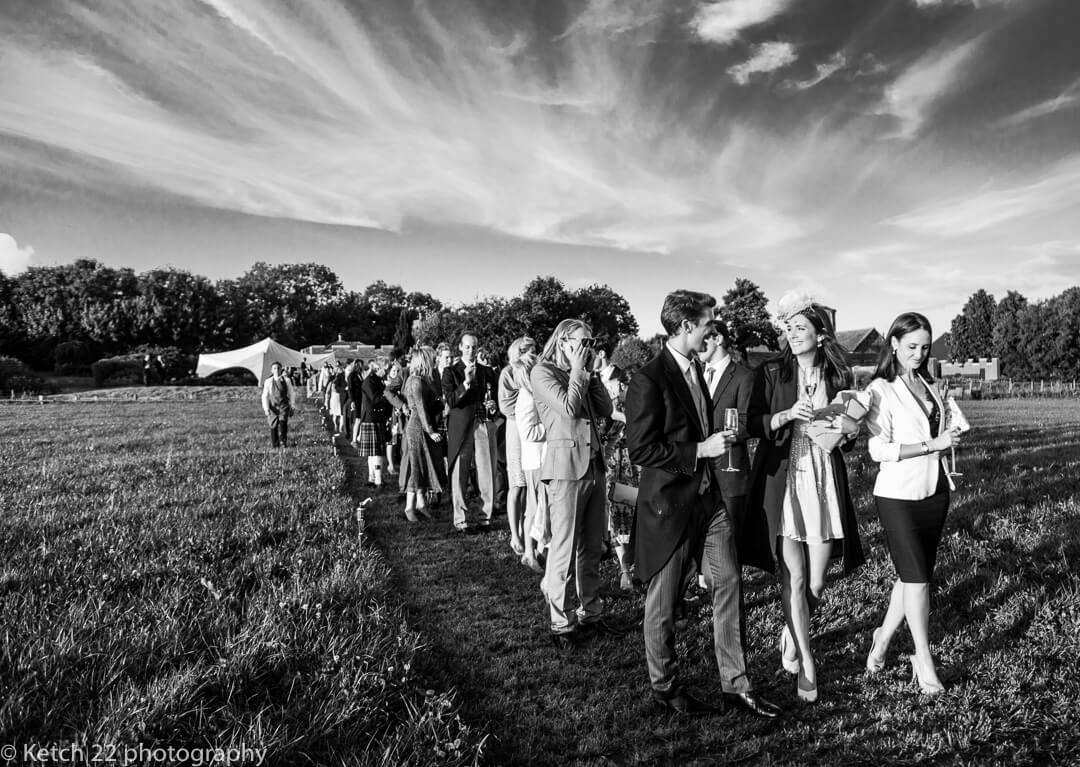 Wedding guests queue for dinner on a summers evening