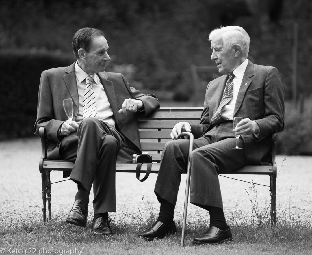 Two grandads sat on bench talking at wedding reception