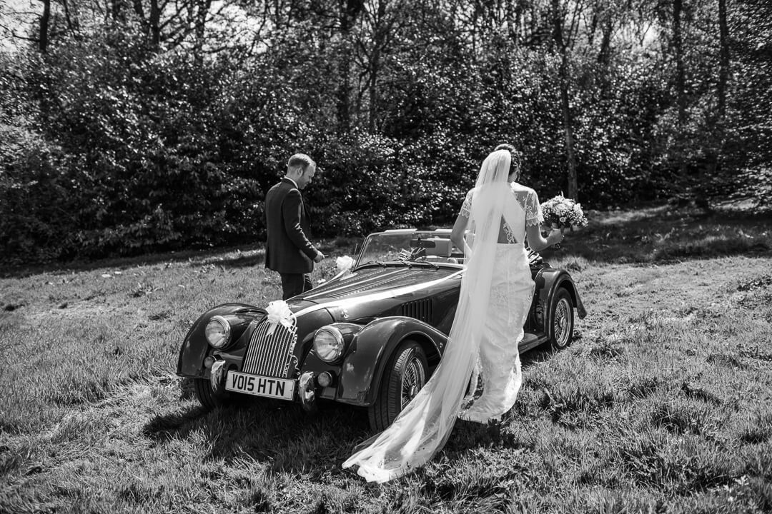 Bride and groom getting into vintage wedding car