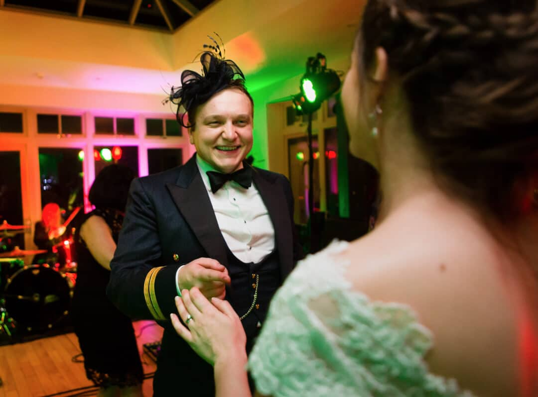 Groom wearing silly hat dancing at wedding reception