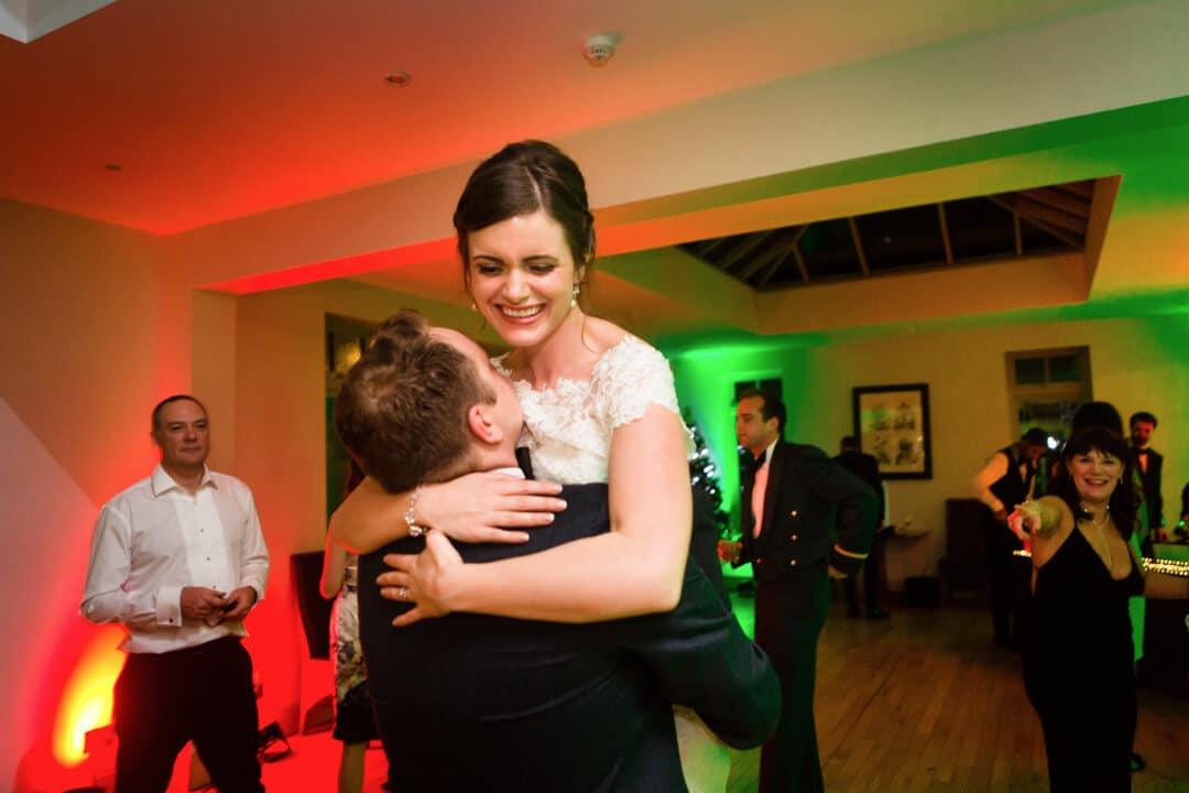 Groom lifting bride off her feet at wedding reception