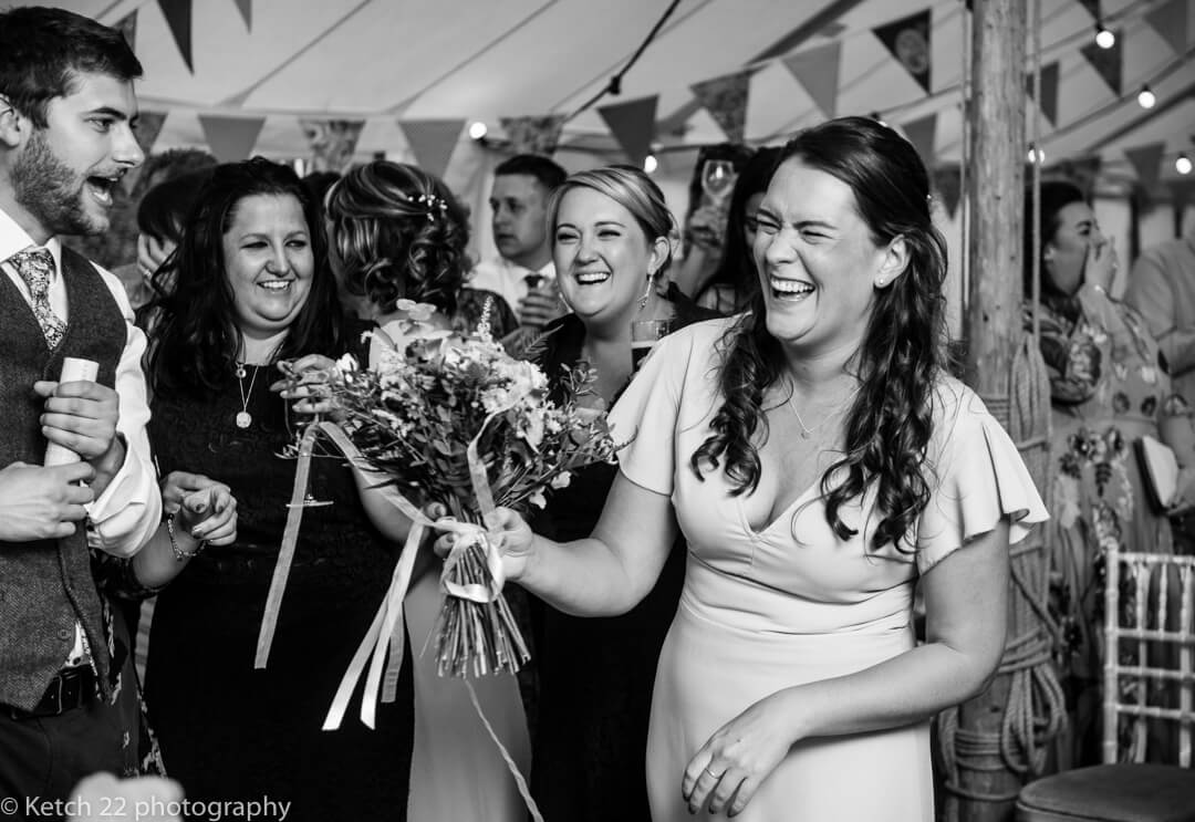 Bridesmaid laughing with captured bouquet at Marquee wedding