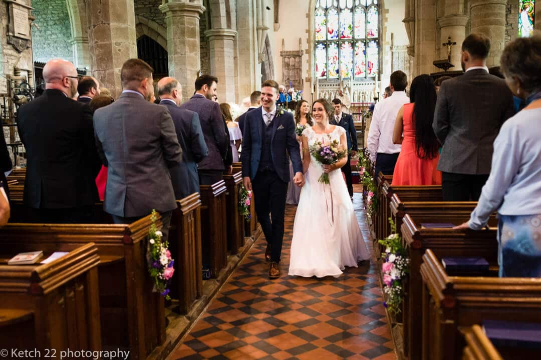 Bride and groom leaving church after Herefordshire wedding ceremony