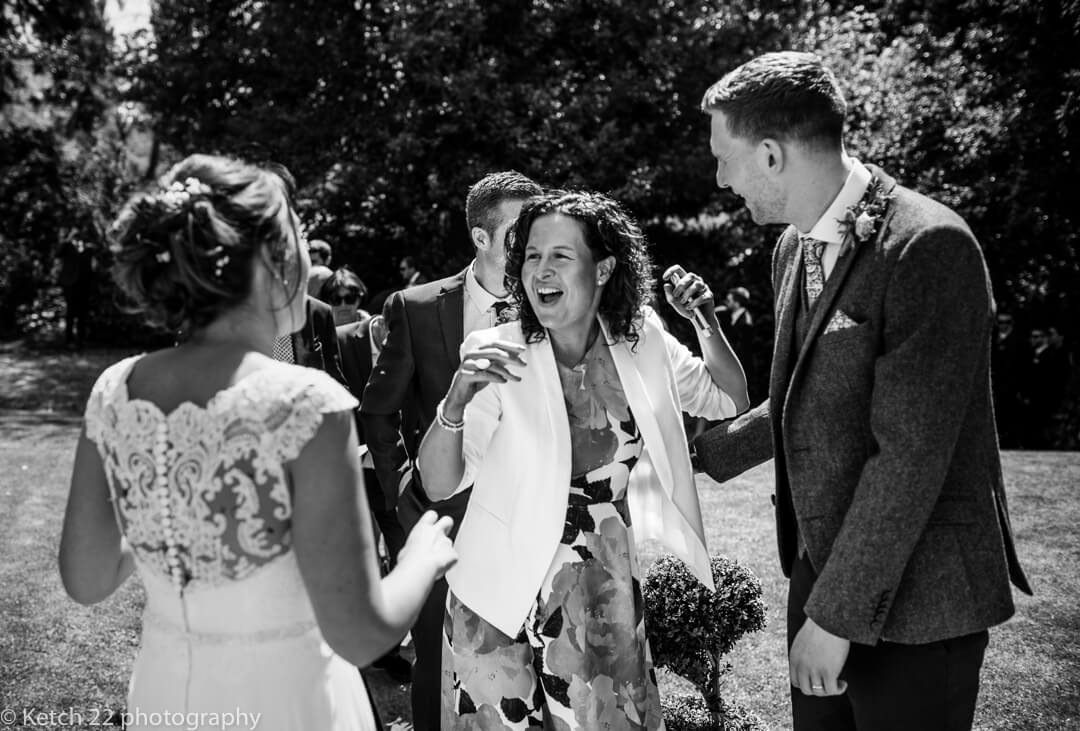 Wedding guests greeting bride