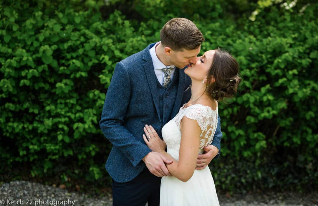 Portrait of bride and groom kissing in front of green bush