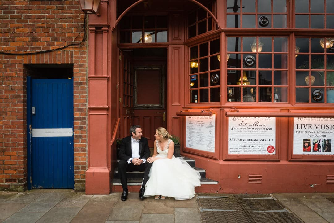 Bride and groom sat on pub steps at The Square Tower Wedding
