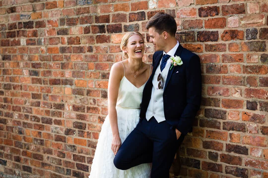 Bride and groom laughing against red brick wall at No 38 wedding Cheltenham