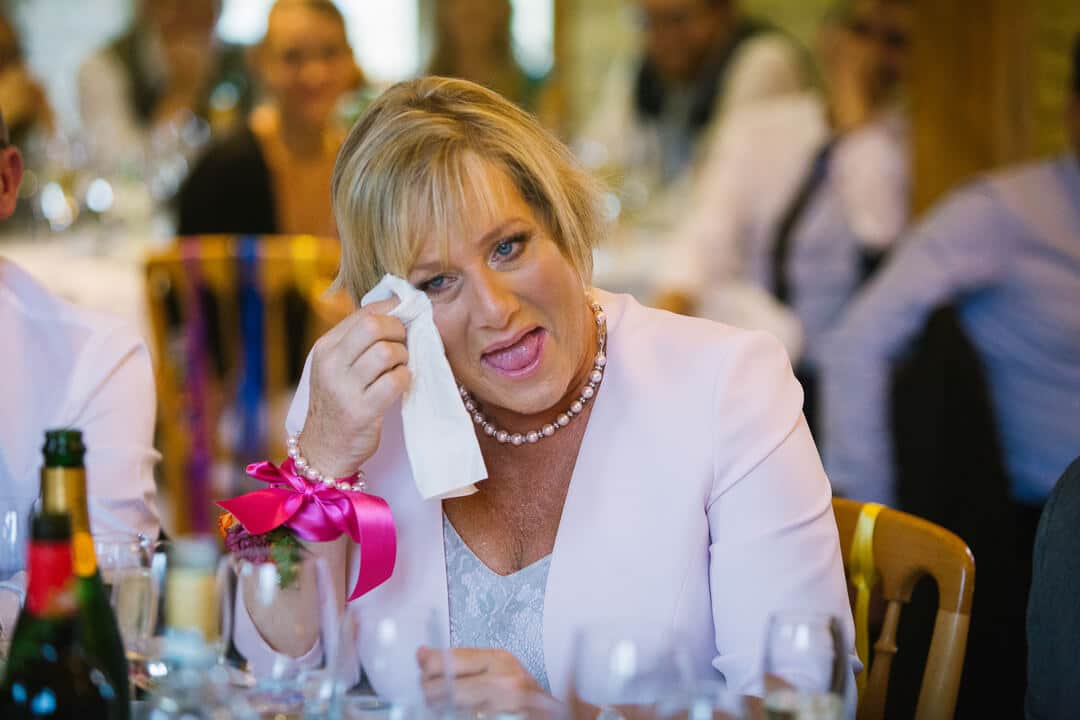 Mother of bride crying with laughter at Wedding speeches
