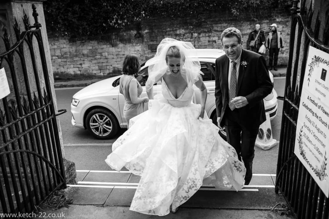 Bride walking to entrance of church with her father