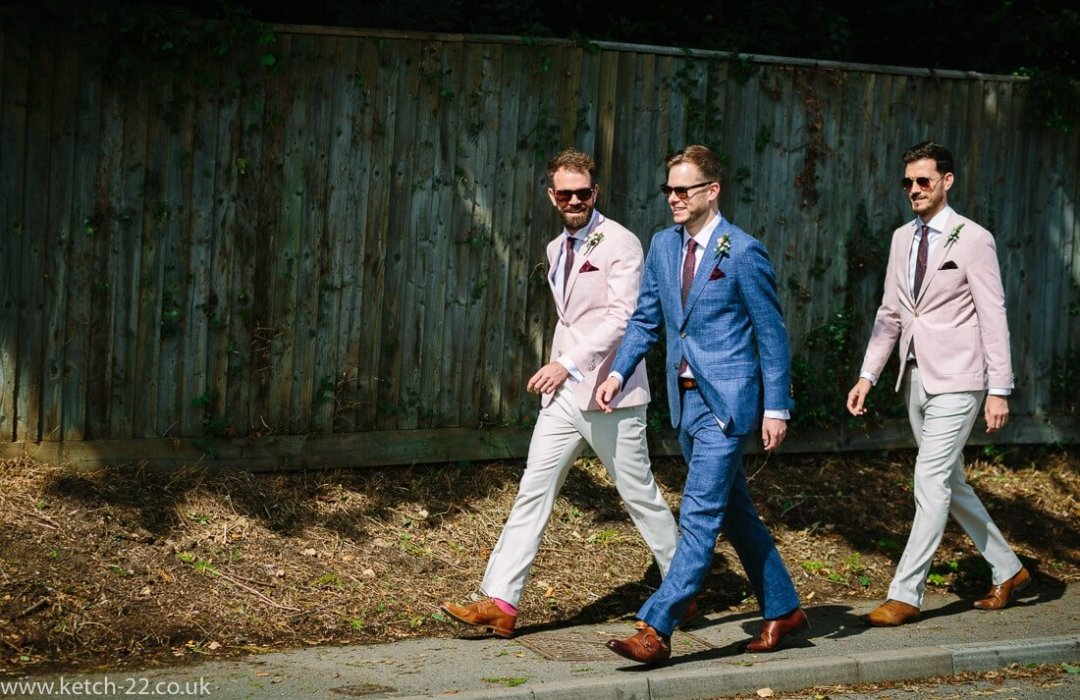Groom and groomsmen walking along street for Winchcombe Gloucestershire wedding