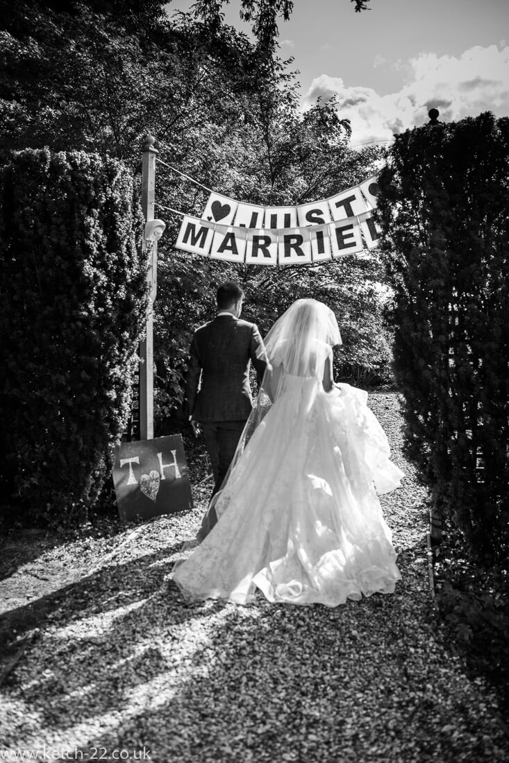Bride and groom walk under just married banner