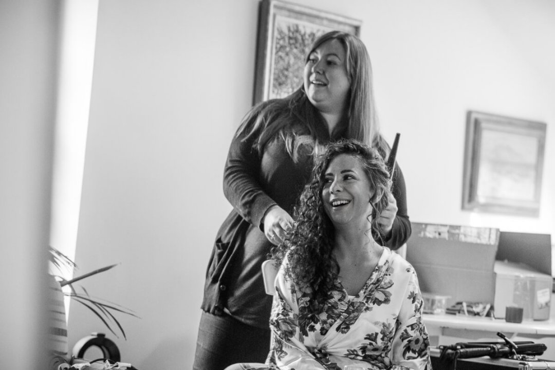 Black and white photo of bride having hair done