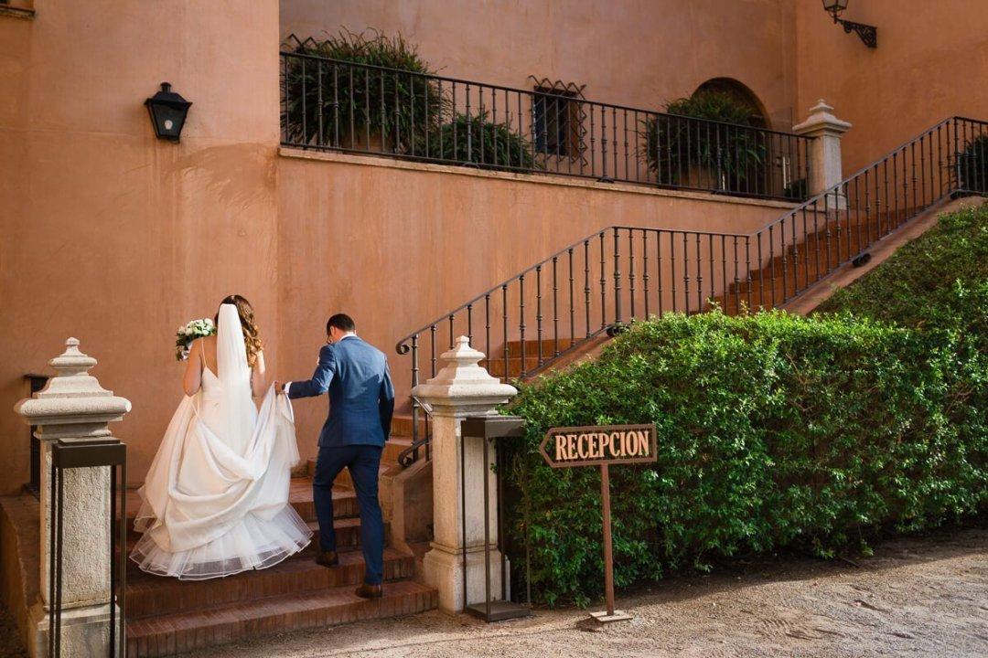 Bride and groom walking up steps at Castillo de Santa Cantalina