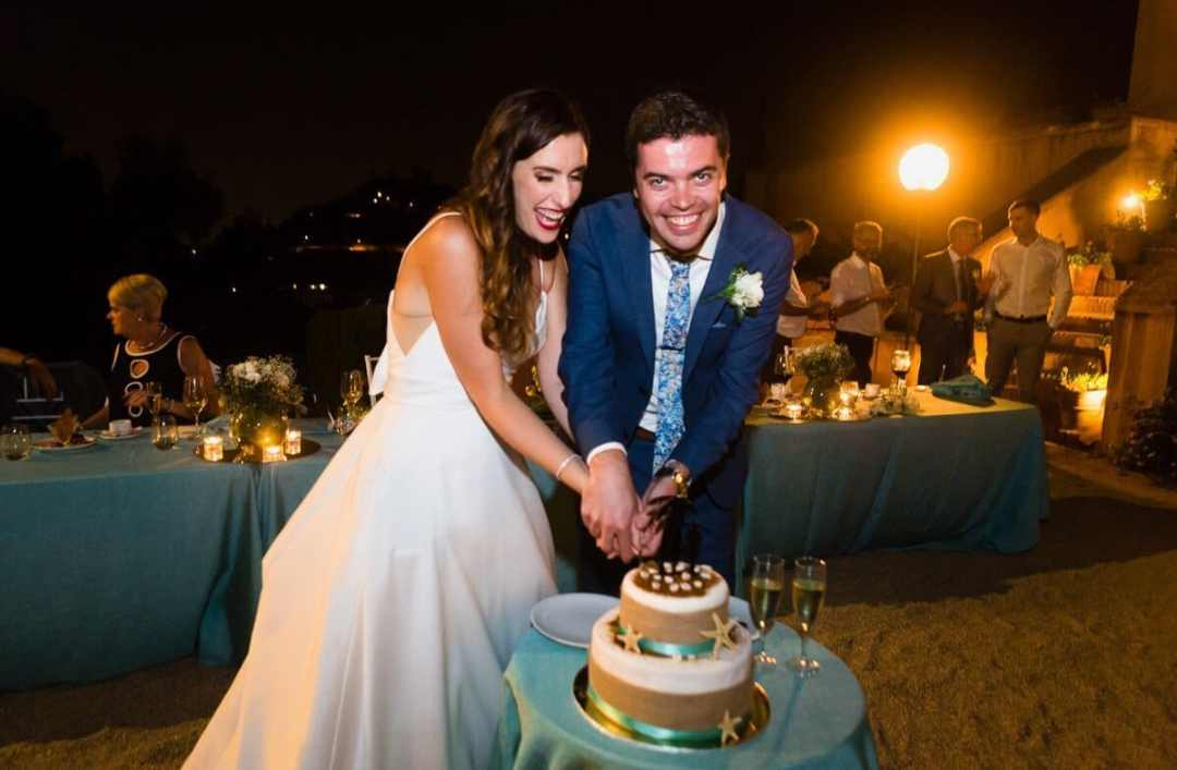 Newly married couple cutting the cake a wedding in Malaga