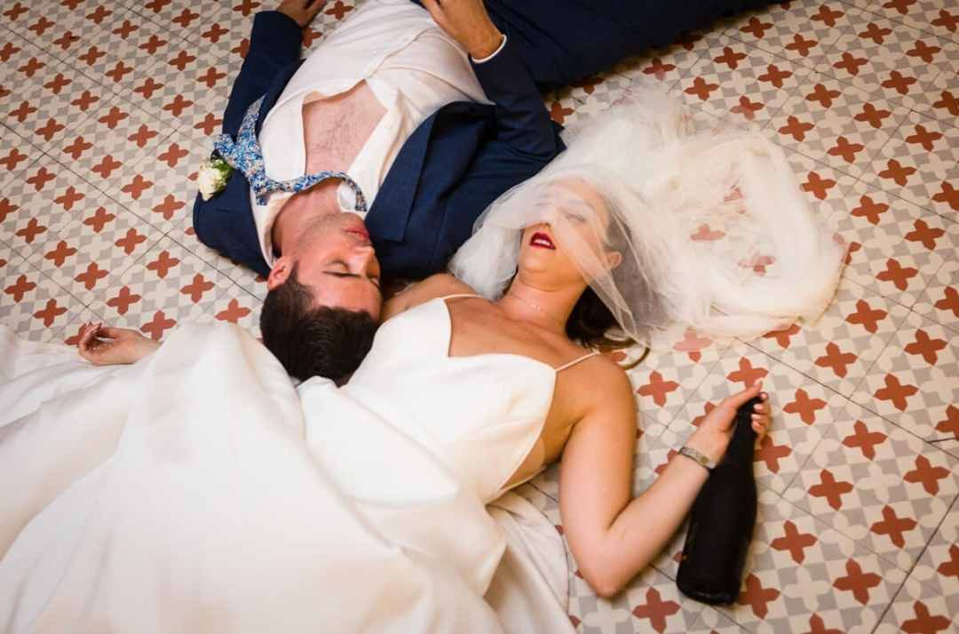 Bride and groom lying on floor drunk and asleep after a long Wedding day