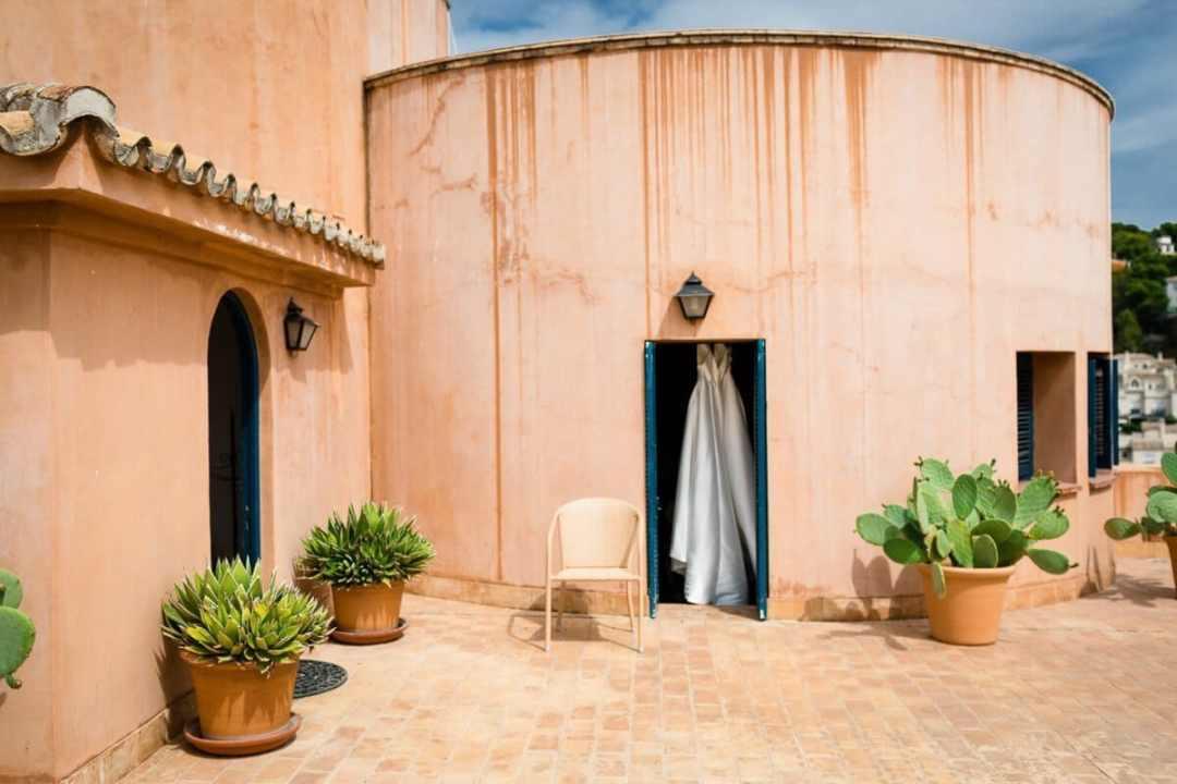 Photo of Wedding dress hanging in doorway in a Spanish Castle