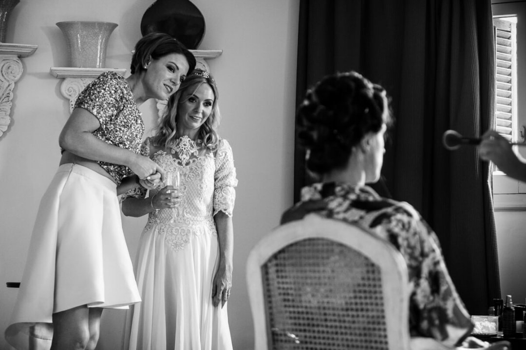 Bridesmaids look on as bride gets ready at Wedding preparations