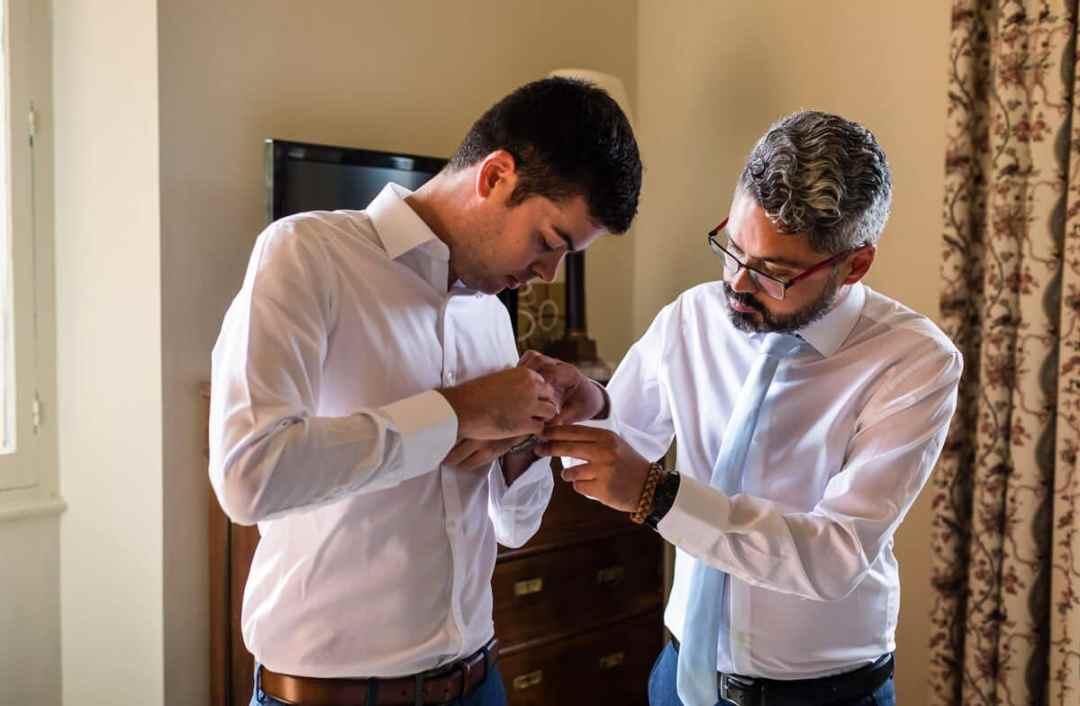 Bestman helps groom get ready at wedding