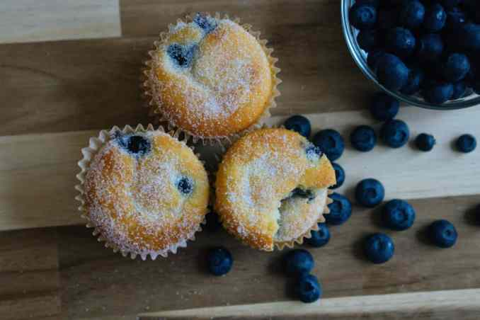 Three sweetener topped blueberry muffins on a cutting board next to blueberries