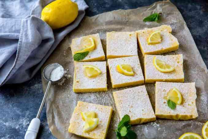 keto lemon bars cut into 9 pieces topped with lemon and mint on parchment paper